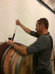 Drinking merlot out of a wooden barrel at Middelvei Winery in South Africa